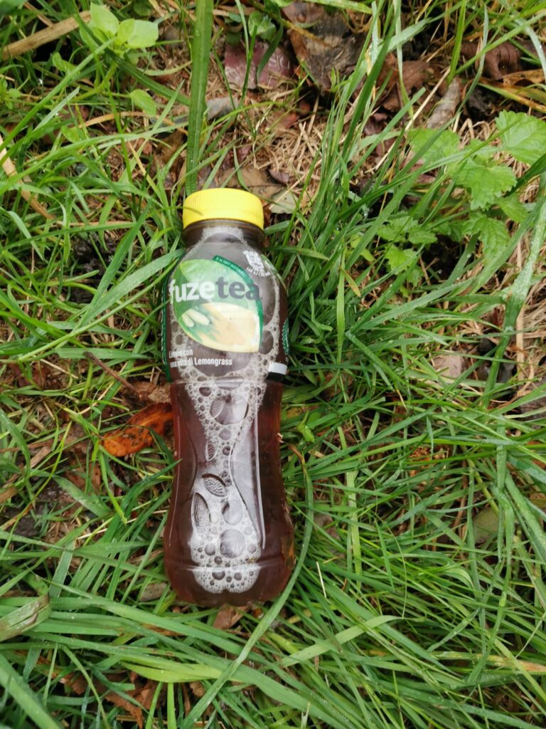 Bottiglietta di the freddo nuova sigillata abbandonata rifiuti a bordo strada